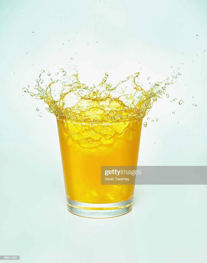 Close up of orange juice splashing out of glass : Stock Photo