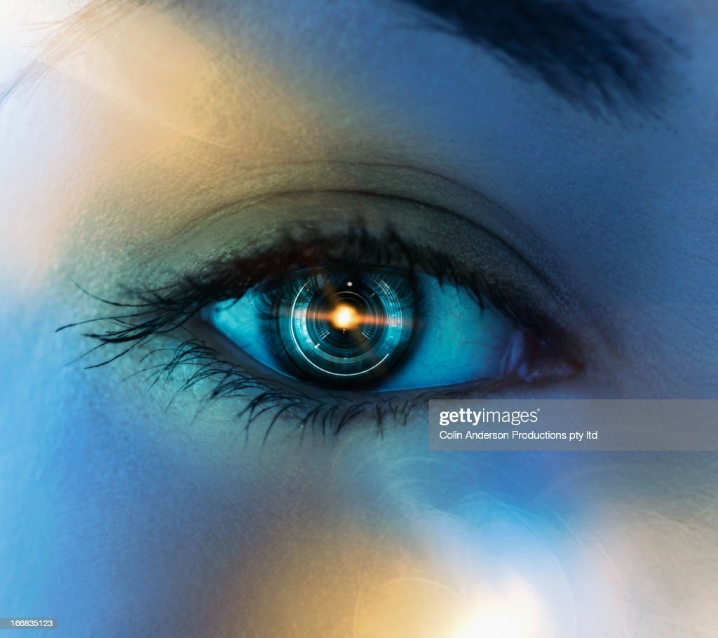 Close up of Pacific Islander woman's eye with mechanical lens : Stock Photo