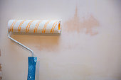 Close up of painter arm painting a wall with paint roller. Copy space