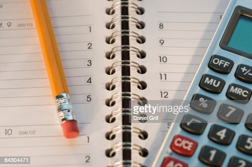 Close up of pencil, notebook and calculator