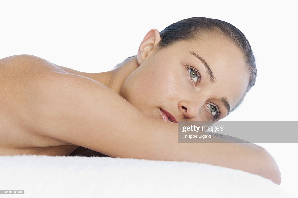 Close up of pensive woman with bare chest laying on towel : Stock Photo