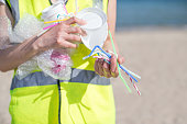 Close Up Of Person Collecting Plastic Waste From Polluted Beach