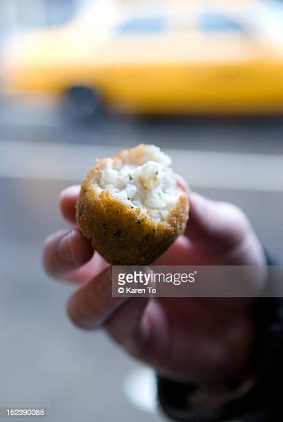 Close up of person holding arancini risotto ball