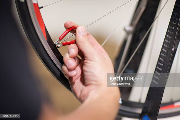 Close up of person using spoke wrench on bicycle wheel