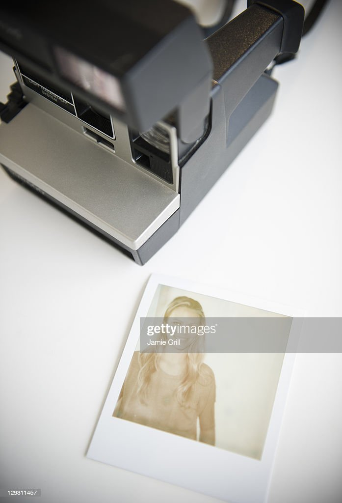 Close up of photograph of woman and polaroid camera : Stock Photo