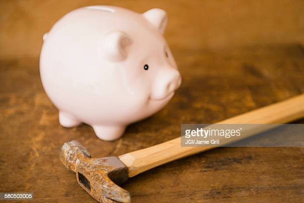 Close up of piggy bank and hammer on table