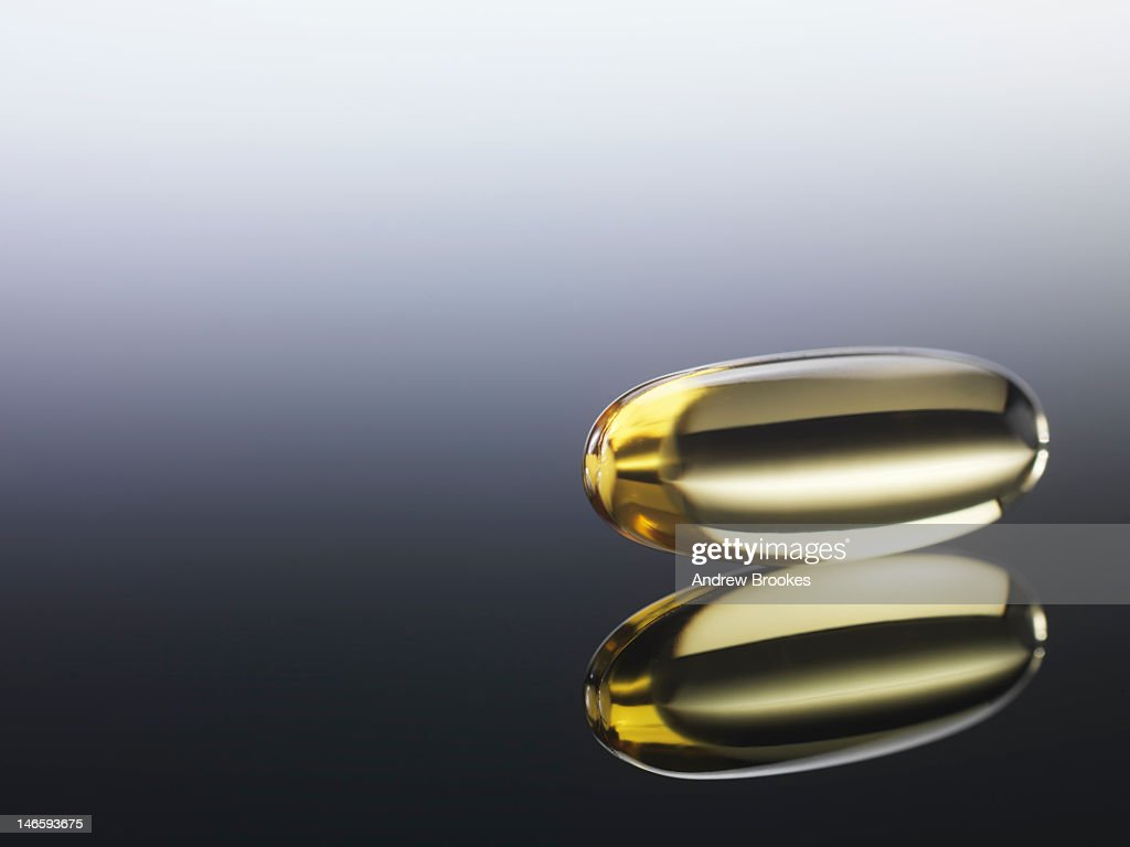 Close up of pill on reflective surface : Stock Photo