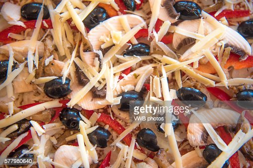 Close up of pizza topping with mushroom, onion, pepper and black olives