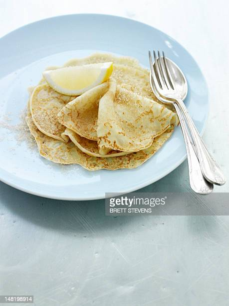 Close up of plate of crepes and lemon
