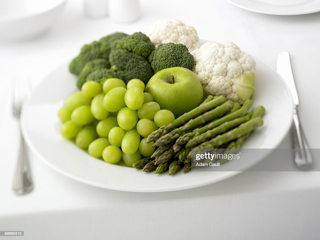 Close up of plate of grapes, asparagus, apple, broccoli and cauliflower : Stock Photo