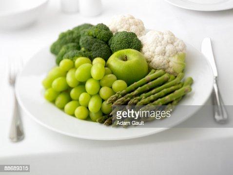 Close up of plate of grapes, asparagus, apple, broccoli and cauliflower : Foto de stock