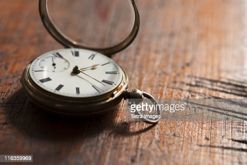 Close up of pocket watch on scratched table