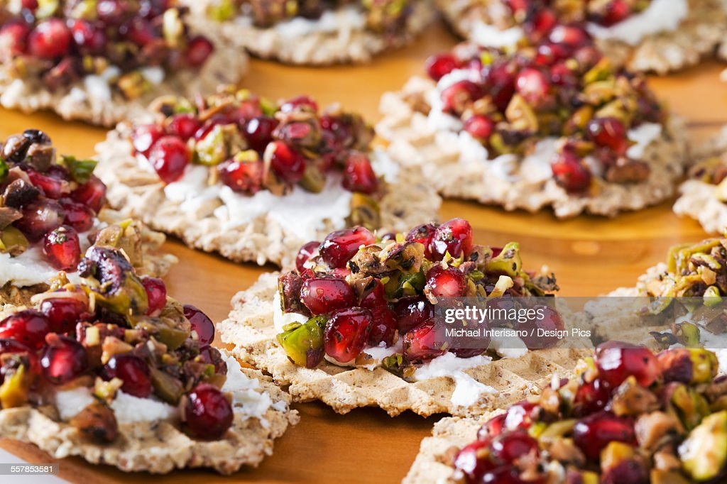 Close up of pomegranate seed and pistachio relish with cream cheese on a cracker