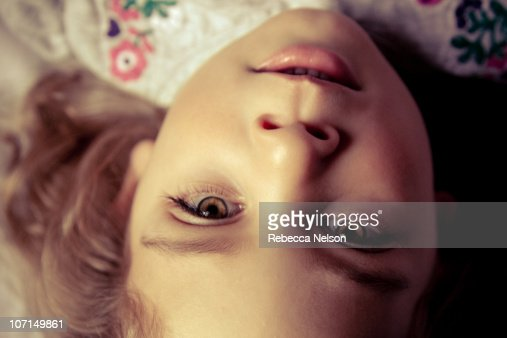 Close up of preschool girl lying on bed : Stock Photo