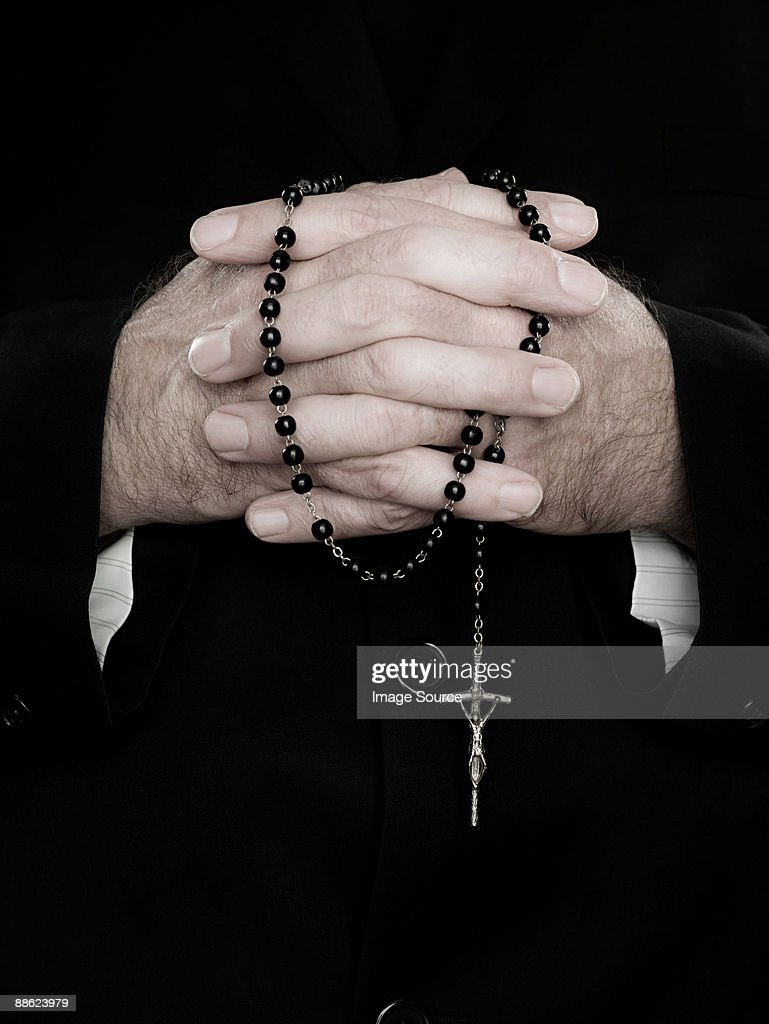 A close up of priest holding prayer beads : Stock Photo