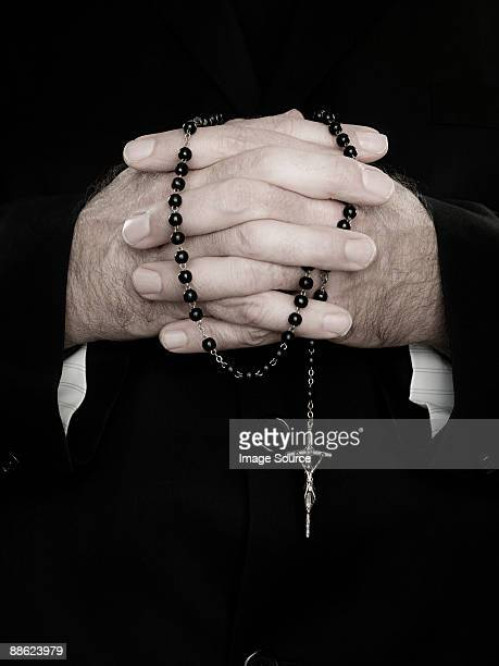 A close up of priest holding prayer beads