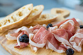 Close up of prosciutto with olives and bread