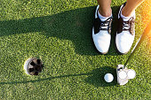 close up of putter hitting golf ball to hole at course.top view Golfer