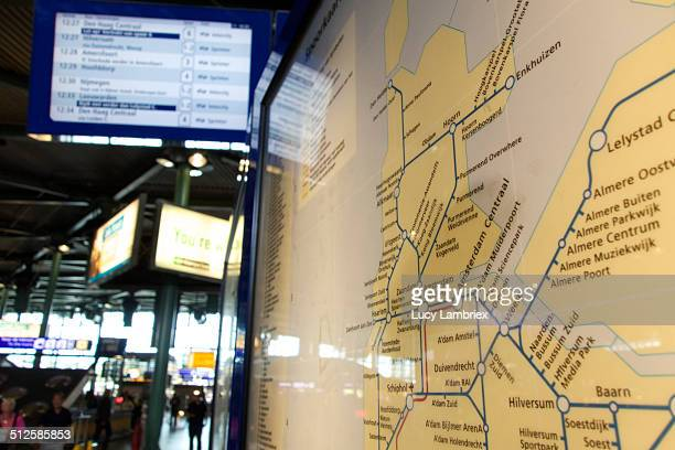 Close up of railway system map in the Netherlands on Schiphol Airport Train station with information monitor and people in background