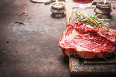 Close up of raw fresh meat Ribeye Steak with herbs and spices on dark rustic metal background, place for text.