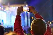 Close up of recording video with smartphone during a concert.