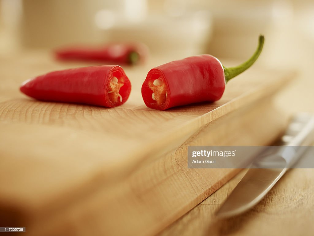 Close up of red chili peppers on cutting board : Stock Photo