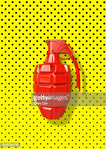 Close up of red grenade on polka dot background