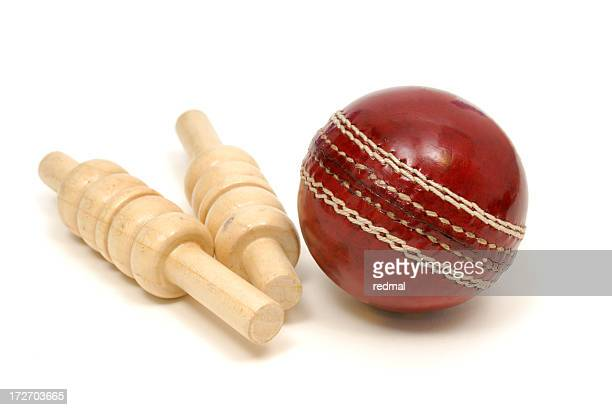 Close up of red leather cricket ball and two wooden bails
