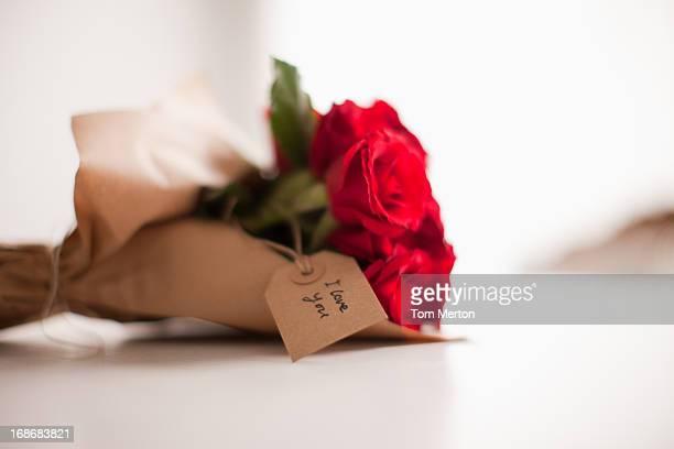 クローズアップの赤いバラとギフトタグ
