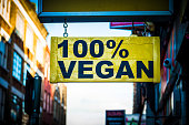 Close up color image depicting a yellow sign on a city street in London, UK, saying in bold black lettering, 100% vegan. Focus is sharp on the sign in the foreground, while the receding street in the