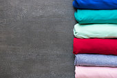 close up of rolled colorful clothes on black background