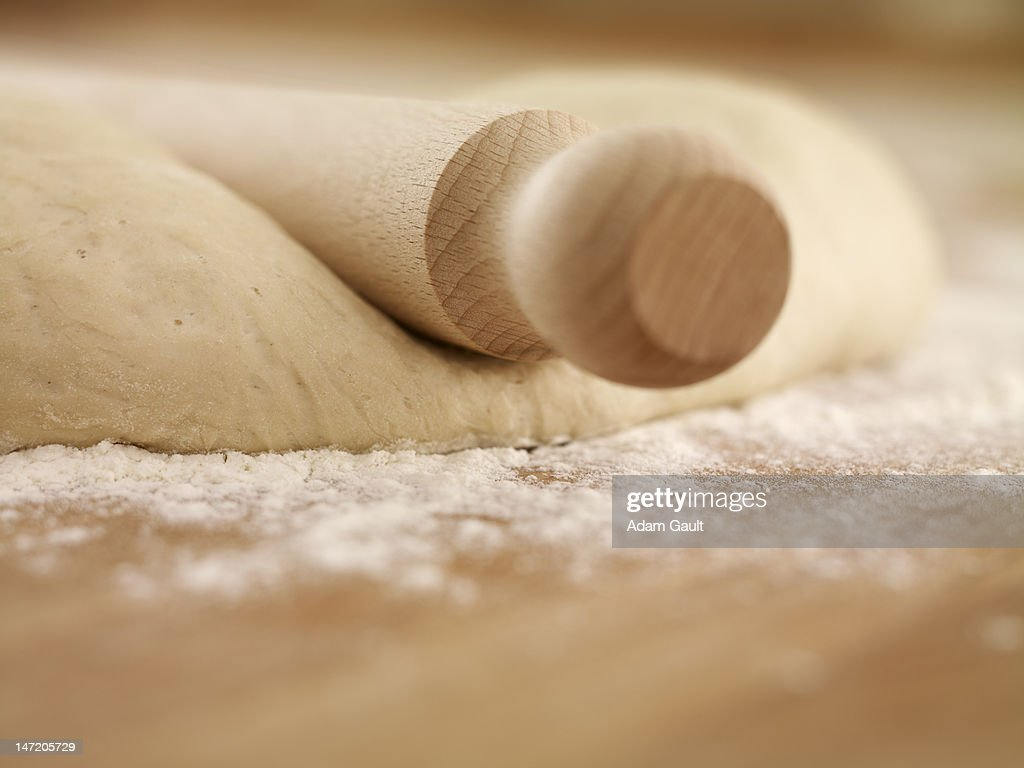 Close up of rolling pin on dough : Stock Photo