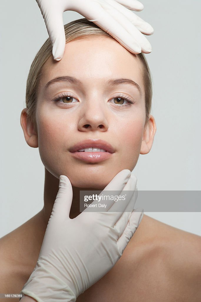 Close up of rubber-gloved hands touching woman's face : Stock Photo
