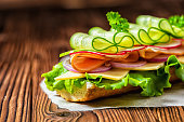 close up of sandwich with ham, cheese, bacon, radish, lettuce, cucumbers and onions on paper, wooden background