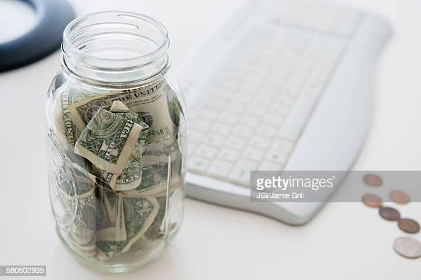 Close up of savings jar near computer keyboard