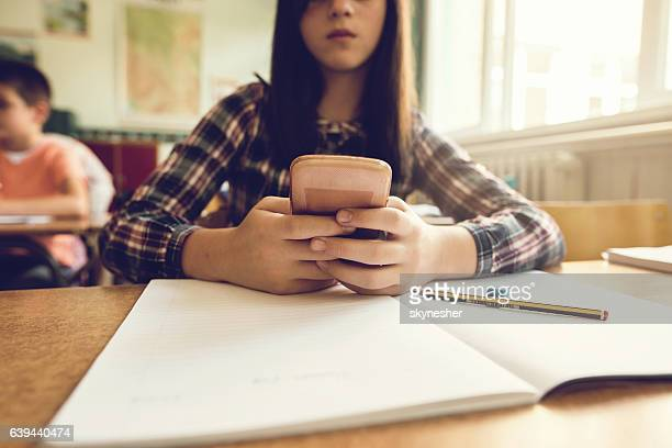 Close up of schoolgirl using mobile phone in the classroom.