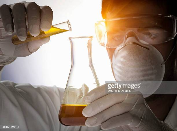 Close up of scientist pouring liquid into flask