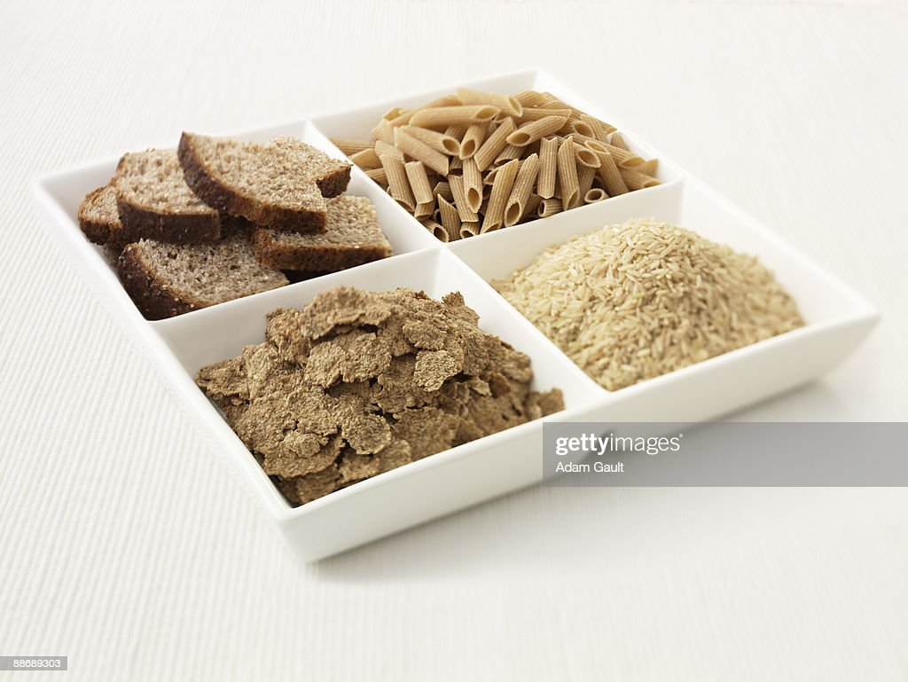 Close up of sectioned plate with bread, pasta, rice and cereal