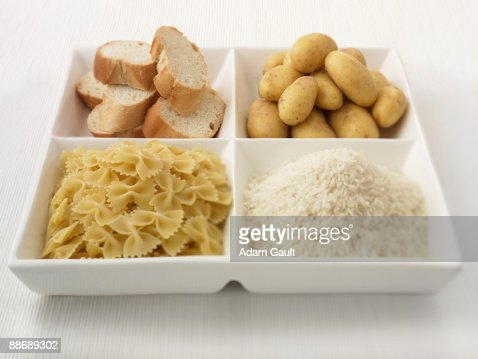 Close up of sectioned plate with bread, potatoes, rice and pasta : Stock Photo