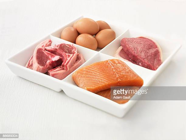 Close up of sectioned plate with eggs, pork, salmon and steak