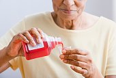 Close up of senior African woman pouring medication into cup