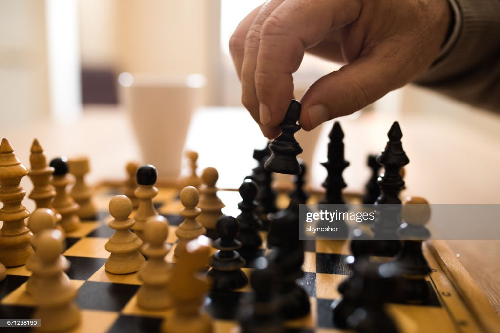 Close up of senior man making a move while playing chess. : Stock Photo