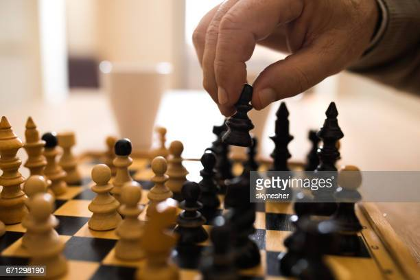 Close up of senior man making a move while playing chess.