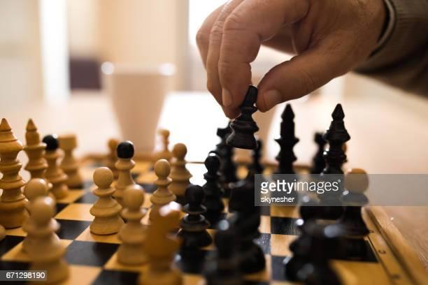 Nahaufnahme von senior Mann macht eine Bewegung beim spielen Schach.