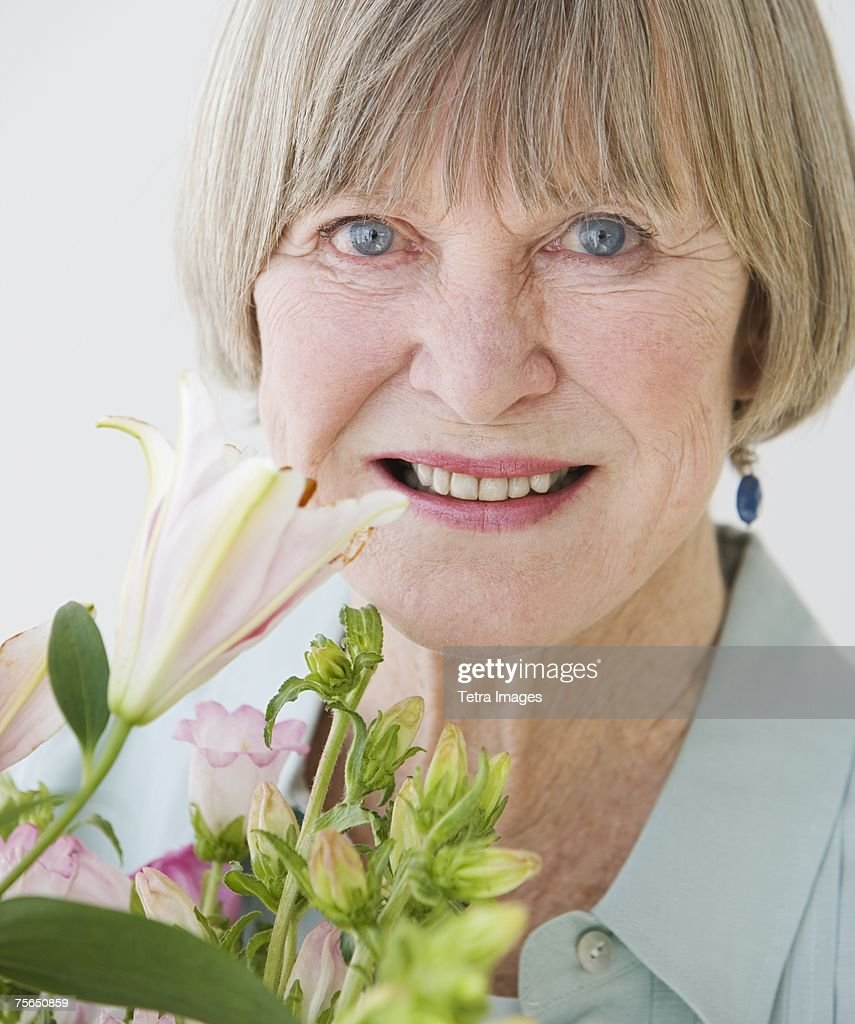 Close up of senior woman and flowers : Stock Photo