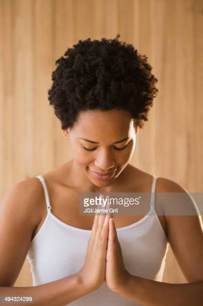 Close up of serene Black woman with hands in prayer position