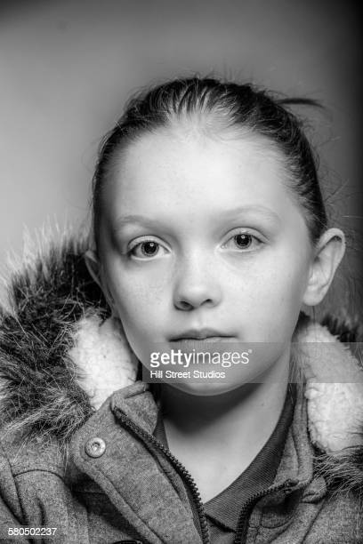 Close up of serious girl wearing coat with fur hood
