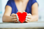 Close up of shiny red heart in young woman's hands, charity concept