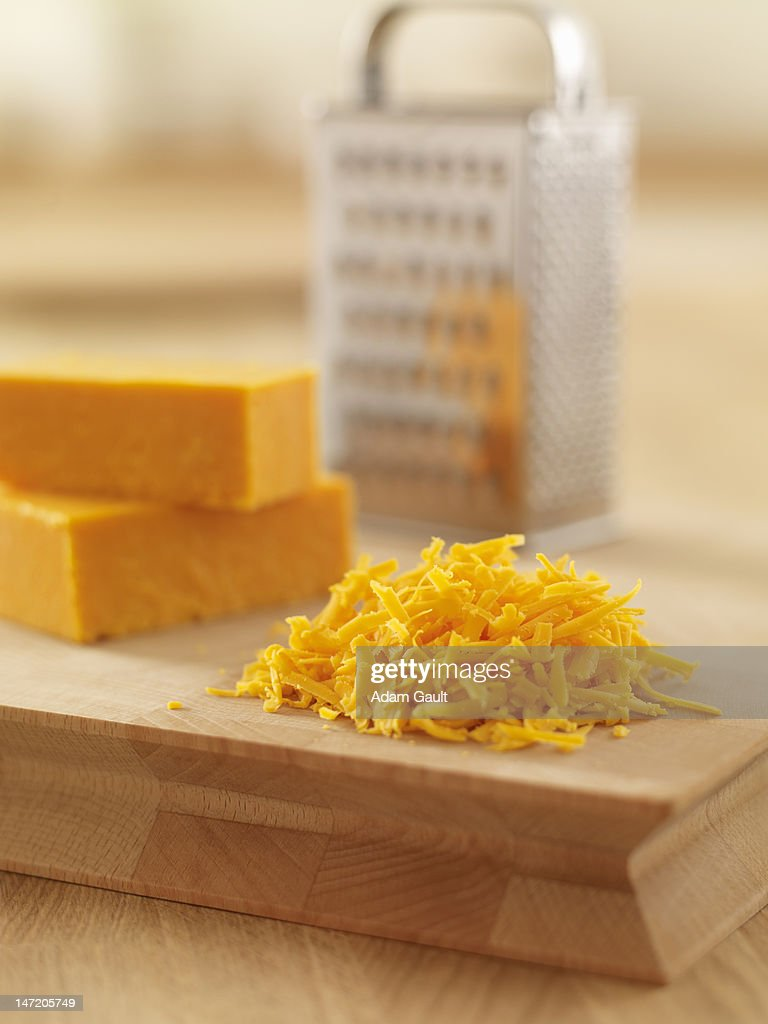Close up of shredded cheese on cutting board : Stock Photo