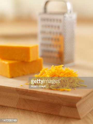 Close up of shredded cheese on cutting board : Stock-Foto